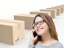 Asian woman talking on mobile phone in warehouse. With cardboard boxes stock photography