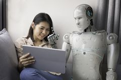 Woman with robot advisor. Asian woman talking to robot while using digital tablet at home royalty free stock photography