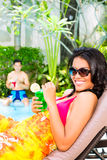 Asian woman tanning at pool with cocktail. Asian woman tanning at pool on sun lounger drinking cocktails Stock Photo
