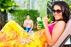 Asian woman tanning at pool with cocktail Stock Photo