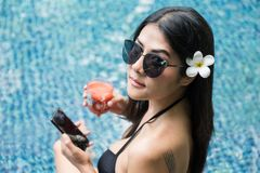 Asian woman with tattoo relax at pool. Top view portrait of sexy Asian beautiful woman with black two piece swimsuit and sunglasses dirnk tomato juice and play Stock Images