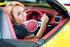 Asian woman testing sports car Stock Photos