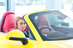 Asian woman testing sports car Royalty Free Stock Photo