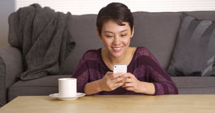 Asian woman texting on smartphone by coffee table Royalty Free Stock Photo