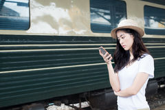 Asian woman texting on smartphone at train station with railway Stock Photo