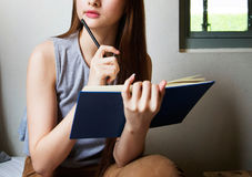 Asian woman thinking with a book.  Stock Photography