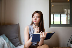 Asian woman thinking with a book.  Royalty Free Stock Photos