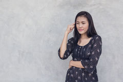 Asian woman thinking on concrete wall background. Royalty Free Stock Photos