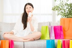Asian woman thinking shopping  online with smartphone Royalty Free Stock Images