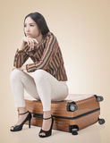 Asian woman thinking and sitting on a luggage Stock Image