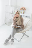 Asian woman thinking while writing on a book Stock Photos
