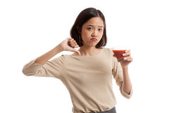 Asian woman thumbs down  hate tomato juice Royalty Free Stock Photos