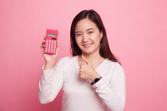 Asian woman thumbs up with calculator. Stock Photos