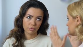 Asian woman tired of empty and stupid chatter of her blonde friend, boredom