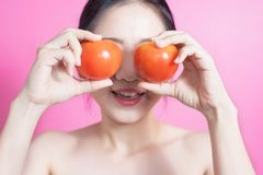 Asian woman with tomato concept. She smiling and holding tomato. Beauty face and natural makeup. Isolated over pink background. royalty free stock image