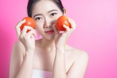 Asian woman with tomato concept. She smiling and holding tomato. Beauty face and natural makeup. Isolated over pink background. Stock Photo