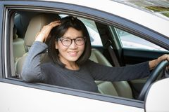 Asian woman toothy smiling face driving sedan car Royalty Free Stock Photos
