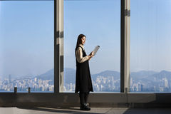 Asian woman with touch pad in hands is standing against skyscraper window background with copy space Royalty Free Stock Photo
