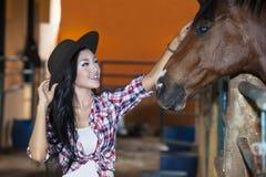 Asian woman touching horse stock photos