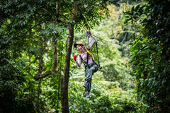 Asian woman TOURIST adult wearing casual clothes Zip Line On Focus FOREST TR stock photo
