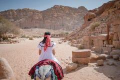 Asian woman tourist riding donkey in Petra, Jordan stock images