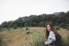 Asian woman tourist walking and trekking along the mountains in tropical forest with feeling happy Stock Photography