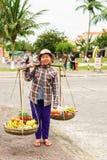 Asian woman trader carrying Rambutan mango banana and mandarin. Hoi An, Vietnam - February 16, 2016: Asian woman trader carrying fresh fruit in bowls on her Royalty Free Stock Photos