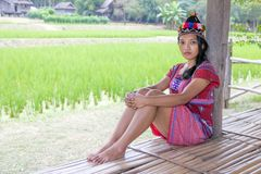 Asian woman in traditional costume for Karen. Resting beside green rice field stock images