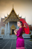 Asian woman in traditional dress holding a red umbrella at Wat B royalty free stock photography