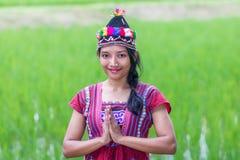 Asian woman in traditional dress on rice field. A young Asian woman in traditional dress doing traditional greeting sawasdee royalty free stock image