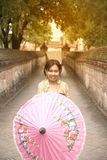 Portrait of Asian female in traditional dresses pose a holding umbrella. Asian woman in traditional dresses holding umbrella at footpath in Wat Mahe Yong royalty free stock photo