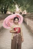 Portrait of Asian female in traditional dresses pose a holding umbrella. Asian woman in traditional dresses holding umbrella at footpath in Wat Mahe Yong stock image