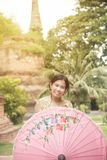 Portrait of Asian female in traditional dresses holding umbrella. Asian woman in traditional dresses holding umbrella near Pagoda in Wat Yai Chai Monkol ancient stock photography