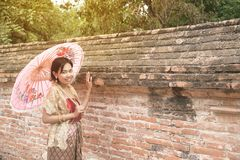 Portrait of Asian female in traditional dresses pose a holding umbrella. Asian woman in traditional dresses holding umbrella near the wall of footpath in Wat royalty free stock photos
