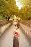 Portrait of Asian female in traditional dresses pose a standing in ancient temple. Asian woman in traditional dresses pose standing at footpath in Wat Mahe Yong royalty free stock photography