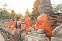 Asian woman in traditional dresses putting orange robe of sitting Buddha. Asian woman in traditional dresses putting orange robe of sitting Buddha statue in Wat royalty free stock image