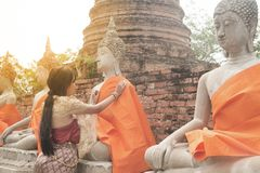 Asian woman in traditional dresses putting orange robe of sitting Buddha. Asian woman in traditional dresses putting orange robe of sitting Buddha statue in Wat royalty free stock photography