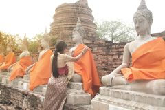 Asian woman in traditional dresses putting orange robe of sitting Buddha. Asian woman in traditional dresses putting orange robe of sitting Buddha statue in Wat stock photography
