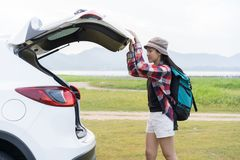 Asian woman travel camping on vacation. A girl open and close back door hatchback car white color on nature green view royalty free stock photos
