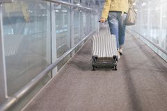 Asian woman traveler dragging carry on luggage suitcase at airport corridor walking to departure gates. Close up royalty free stock photos