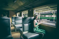 Asian woman traveler has drinking coffee in the train with happiness at Hua Lamphong station at Bangkok, Thailand. Adult blue book brown business caucasian cup royalty free stock photography
