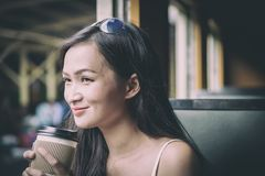 Asian woman traveler has drinking coffee in the train with happiness at Hua Lamphong station at Bangkok, Thailand. Adult blue book brown business caucasian cup stock photography