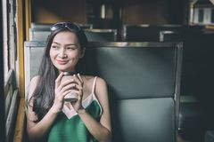 Asian woman traveler has drinking coffee in the train with happiness at Hua Lamphong station at Bangkok, Thailand. Adult blue book brown business caucasian cup royalty free stock photo