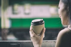 Asian woman traveler has drinking coffee in the train with happiness at Hua Lamphong station at Bangkok, Thailand. Adult blue book brown business caucasian cup stock photo