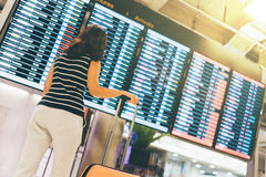 Asian woman traveler looking at flight information screen in an airport, holding suitcase, travel or time concept. Warm light effect Royalty Free Stock Photography