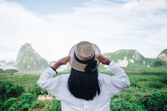 Asian woman traveler wearing a white shirt holding hat and looking at Samed Nang Chee amazing mountains and forest, travel. Holiday relaxation concept royalty free stock photo