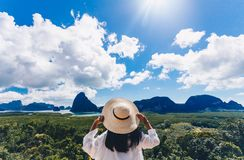 Asian woman traveler wearing a white shirt holding hat and looking at Samed Nang Chee amazing mountains and forest, travel. Holiday relaxation concept stock photography