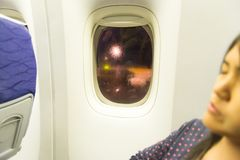 Asian woman traveller sleeping siting near window on airplane during flight. At night time Royalty Free Stock Images