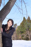 Asian woman beside tree trunk Royalty Free Stock Image