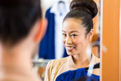 Asian Woman trying clothes in shop mirror Stock Photo